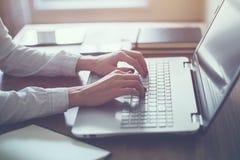 工作在键盘的家庭办公室手上的妇女 库存图片