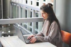 工作在键盘膝上型计算机的咖啡馆手的妇女 免版税图库摄影