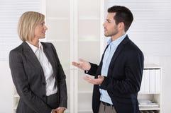工作在队的两个商人一起谈话在  免版税图库摄影
