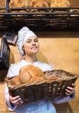 工作在面包店的女店员用面包和另外酥皮点心 库存图片
