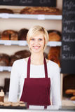工作在面包店的年轻女推销员 库存图片
