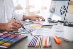 工作在项目建筑图画和颜色样片,在图表图的选择着色的年轻创造性的图表设计师 免版税库存照片