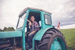 工作在领域的拖拉机,妇女的异常的工作,男女平等概念的年轻美丽的女孩 免版税库存照片