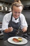 工作在餐馆厨房里的实习生厨师 免版税库存图片