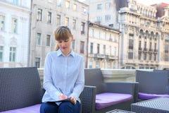 工作在餐馆大阳台的可爱的女实业家 免版税库存照片