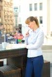 工作在餐馆大阳台的年轻可爱的女实业家。 免版税库存照片