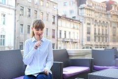 工作在餐馆大阳台的年轻女实业家。 库存图片