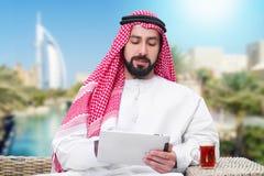 工作在移动片剂&饮用的茶的阿拉伯人 免版税图库摄影