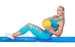 工作在仰卧起坐锻炼的适合的妇女 免版税库存图片