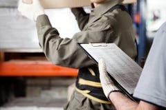 工作在仓库的工头和监督员 免版税库存照片