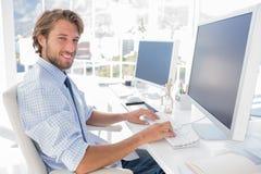 工作在他的书桌的微笑的设计师 免版税库存照片