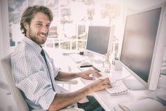 工作在他的书桌的微笑的设计师 免版税库存图片