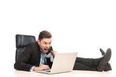 工作在他的便携式计算机的恼怒的商人 库存照片