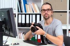 工作在他的办公室的摄影师 免版税图库摄影