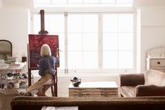 工作在绘画的女性艺术家在明亮的白天演播室 免版税库存图片