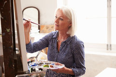 工作在绘画的女性艺术家在演播室 库存图片