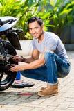 工作在他的小型摩托车的亚裔人 免版税库存照片