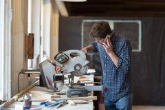 工作在他的工艺的木匠在一个多灰尘的车间 库存照片