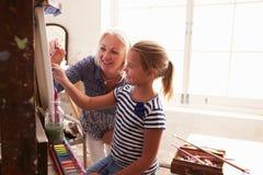 工作在绘画的母亲和女儿在艺术演播室 免版税库存照片