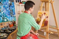 工作在他的演播室的男性艺术家 免版税库存照片