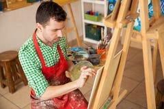 工作在他的演播室的年轻艺术家 免版税库存照片