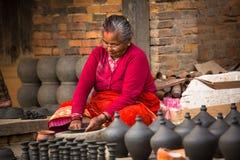 工作在他的瓦器车间的尼泊尔妇女,在Bhaktapur,尼泊尔 免版税库存照片