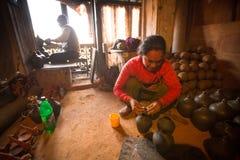 工作在他的瓦器车间的未认出的尼泊尔妇女 库存图片