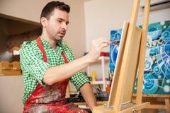 工作在绘画的英俊的艺术家 库存图片