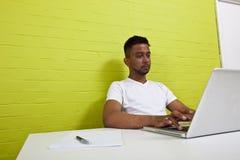 工作在他的计算机的年轻印地安人 免版税库存图片