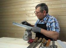 工作在他的车间的资深木匠 免版税库存图片