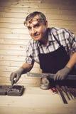 工作在他的车间的资深木匠 免版税库存照片