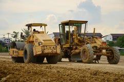 工作在建造场所的机器和人们 免版税库存照片