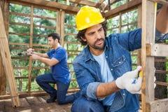 工作在建造场所的建筑工人 免版税库存图片