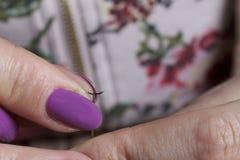工作在头饰的妇女 布料缝合的花  免版税库存图片