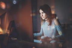 工作在coworking的办公室的可爱的少妇在晚上 使用当代台式计算机的女孩,被弄脏 库存照片