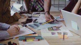 工作在coworking的空间的年轻多种族人 谈论的建筑师小起动项目想法 股票录像