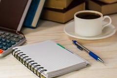 工作场所会计 有一个笔记薄的计算器在振作起来的热的咖啡旁边 免版税库存图片