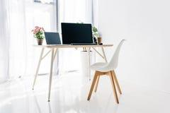 工作场所内部有椅子、盆的植物、膝上型计算机和计算机的 库存照片