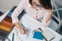 工作场所妇女设计师长帷幕和选择织品顶视图内部的 免版税库存图片