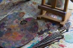 工作场所有颜色和刷子的画家调色板 颜色调色板,创造性的混乱,艺术 免版税库存图片