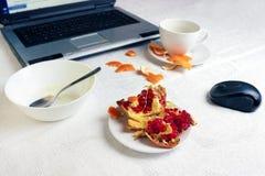 工作场所照片在早餐A咖啡的与膝上型计算机的以后在白色桌布,有粥残羹剩饭的空的碗,一半  库存图片