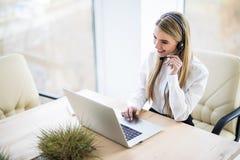 工作场所的愉快的微笑的女性用户支持电话操作员 图库摄影