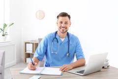 工作场所的男性医学助理诊所的 免版税库存图片