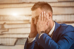 工作场所的疲乏的商人在拿着他的在手上的办公室头 清早困工作者在夜间工作以后 免版税库存图片
