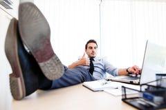工作场所的-作为诱导姿态的赞许年轻疲乏的商人 免版税图库摄影