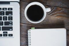 工作场所自由职业者或程序员或者设计师 一杯咖啡、一台膝上型计算机和一个笔记本,在一张木桌上 水平的框架 库存图片