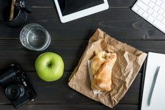 工作场所顶视图用苹果、被咬住的小圆面包、杯水和数字式设备 库存图片