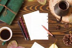工作场所顶视图 与纸笔记的,牛奶店, cofee, Ñ  ezve,锥体,秋叶的木背景 免版税库存图片