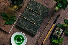 工作场所画家和绿色叶子 介绍 空白的笔记本 春天空白笔记本 免版税图库摄影