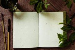 工作场所画家和绿色叶子 介绍 空白的笔记本 春天空白笔记本 免版税库存照片